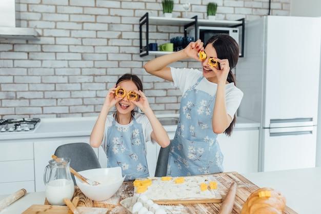 Deux soeurs jouant avec des formes pour cuire dans la cuisine ! du temps en famille!