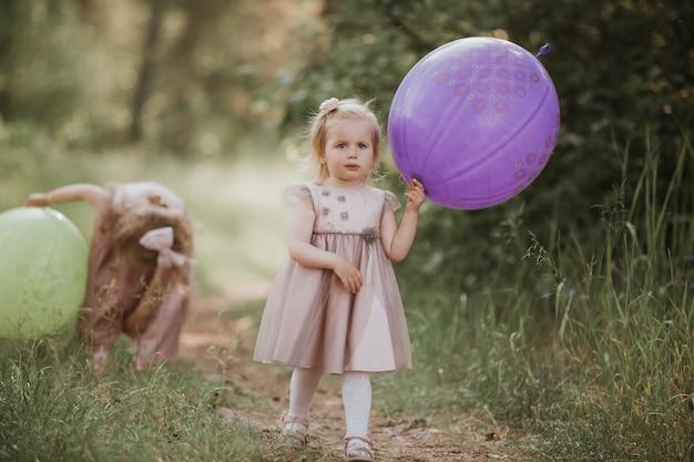 Deux sœurs jouent aux ballons. enfants jouant ensemble. soeur heureuse avec des ballons marchant sur le champ de printemps