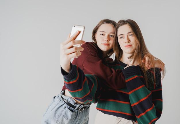 Deux soeurs jumelles belles filles en casual faire selfie
