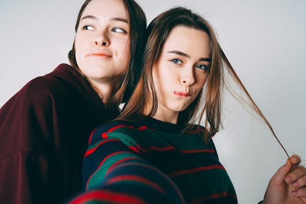 Deux soeurs jumelles belles filles en casual prenant selfie