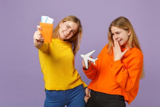Deux sœurs jumelles blondes gaies vêtues de vêtements colorés détiennent un passeport, un billet d'embarquement, un avion en papier isolé sur un mur bleu violet. concept de mode de vie familial de personnes.