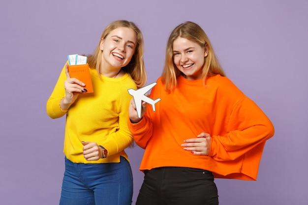 Deux sœurs jumelles blondes riantes vêtues de vêtements colorés détiennent un passeport, un billet d'embarquement, un avion en papier isolé sur un mur bleu violet. concept de mode de vie familial de personnes.
