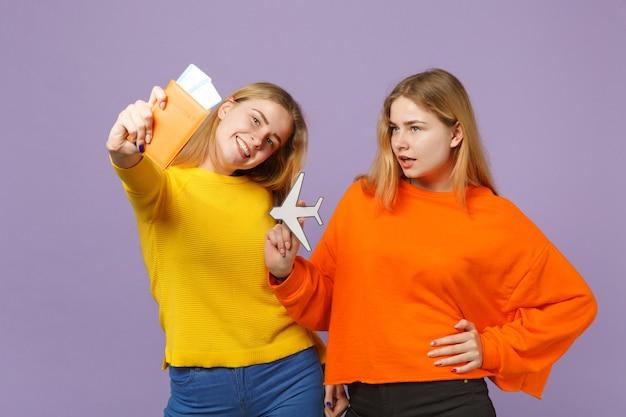 Deux sœurs jumelles blondes souriantes vêtues de vêtements colorés détiennent un passeport, un billet d'embarquement, un avion en papier isolé sur un mur bleu violet. concept de mode de vie familial de personnes.
