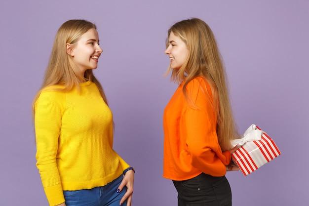 Deux sœurs jumelles blondes souriantes vêtues de vêtements vifs tiennent une boîte cadeau à rayures rouges avec un ruban cadeau isolé sur un mur bleu violet. anniversaire de la famille des gens, concept de vacances.