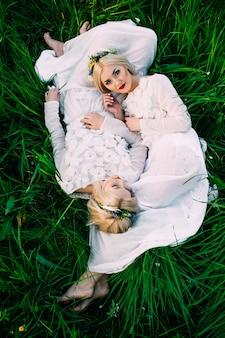 Deux soeurs jumelles couché sur l'herbe verte