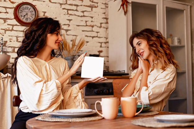 Deux soeurs jumelles dans la plaque blanche de cadeau de cuisine