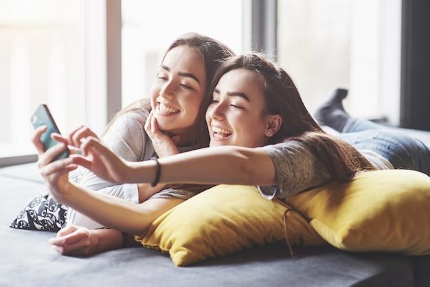 Deux soeurs jumelles souriantes mignonnes tenant le smartphone et faisant selfie. filles allongées sur le canapé posant et joie