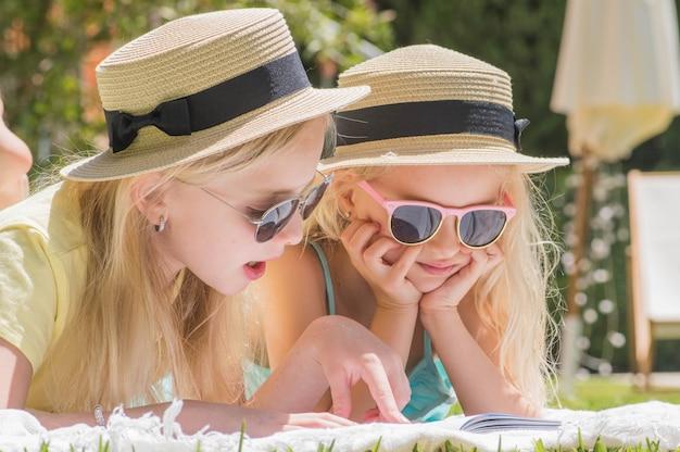 Deux sœurs lisant un livre d'intérêt dans le jardin, plaisir d'été