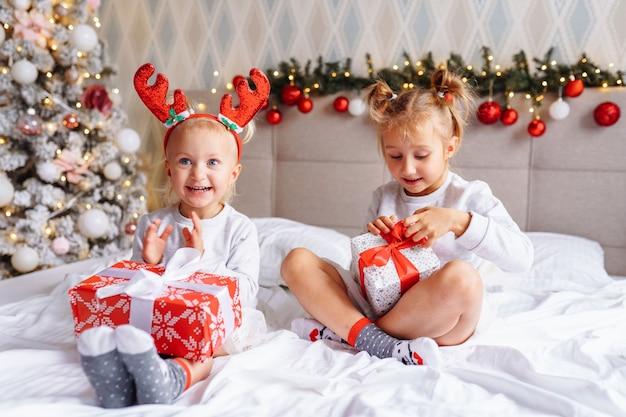 Deux soeurs mignonnes de filles avec des cadeaux de noël s'asseyent sur le lit à la maison dans la salle décorée de noël. enfants heureux, réveillon de noël.