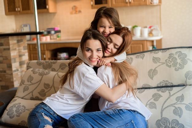 Deux soeurs et petite fille souriant et serrant à l'intérieur de la maison.