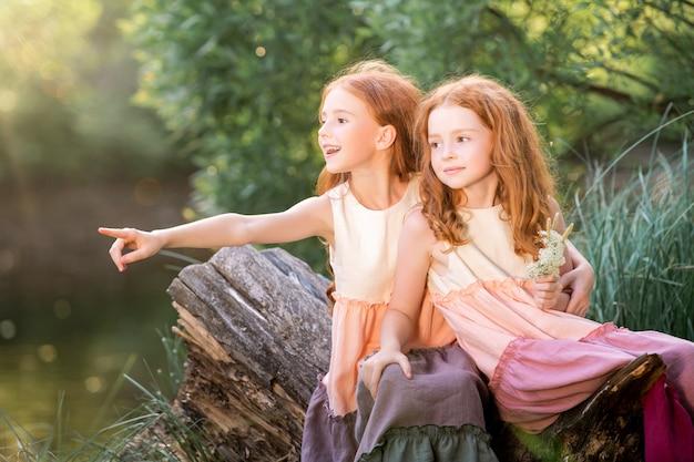 Deux sœurs rousses vêtues de longues robes en lin se reposent sur le lac du parc par une journée d'été ensoleillée. une fille pointe sa main en direction du lac.
