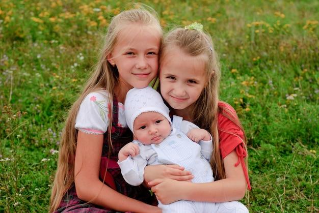 Deux sœurs s'embrassent et petit frère à l'extérieur, famille heureuse