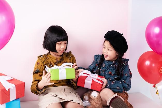 Deux soeurs se font échanger un cadeau ensemble, avec le sourire et le bonheur