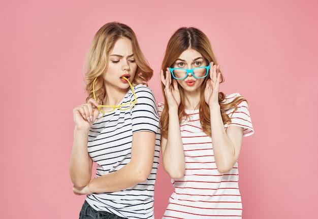 Deux sœurs se tiennent côte à côte fashion studio lifestyle vue recadrée fond rose amitié