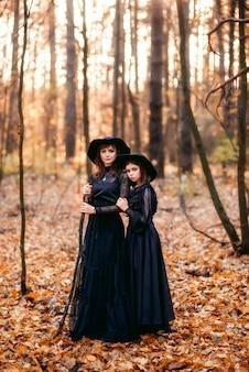 Deux sorcières dans la forêt d'automne. mère et fille en robes noires