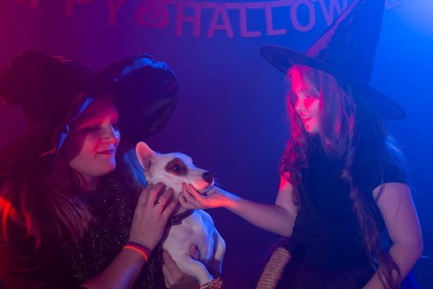 Deux sorcières d'halloween faisant de la magie avec un chien jack russell terrier dans la nuit d'halloween. magie, vacances et concept mystique.