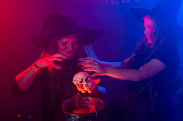 Deux sorcières d'halloween faisant une potion et évoquant des vacances magiques de nuit d'halloween et mystique