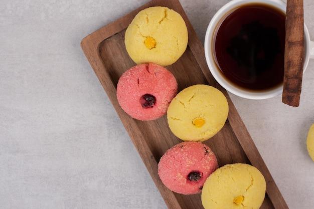 Deux sortes de biscuits et tasse de thé sur tableau blanc.