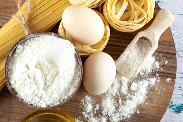 Deux sortes de pâtes crues avec de l'huile, des œufs et un bol de farine sur une planche de bois.