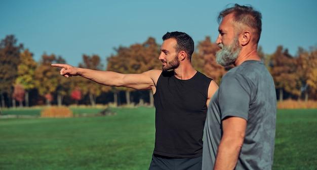 Les deux sportifs debout à l'extérieur et faisant des gestes