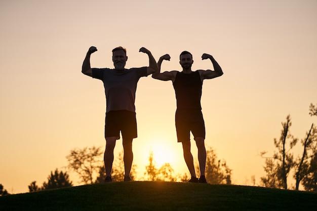 Les deux sportifs montrent des muscles sur fond de coucher de soleil