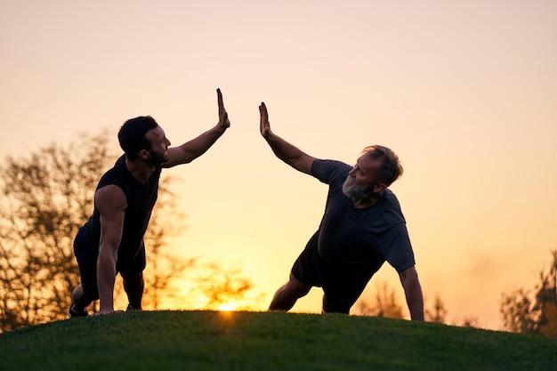 Les deux sportifs poussent ensemble sur fond de coucher de soleil