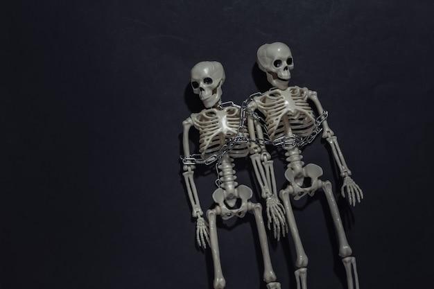 Deux squelettes enroulés dans une chaîne sur fond noir foncé.