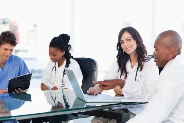 Deux stagiaires médicaux souriants travaillant à l'ordinateur près de collègues