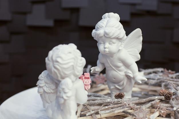Deux statues d'anges avec des ailes et une couronne de brindilles sur fond sombre pour noël