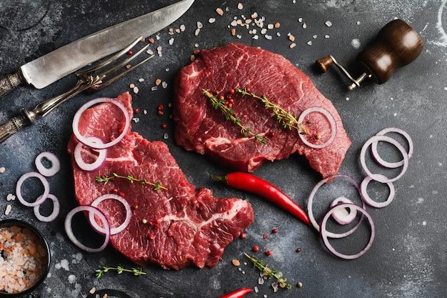 Deux steak de boeuf cru aux épices, oignons et piment sur fond d'ardoise foncée ou de béton. vue de dessus