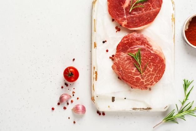 Deux steak crue parisienne frais sur papier parchemin blanc avec sel, poivre et romarin dans un style rustique sur fond de bois ancien. black angus. vue de dessus.
