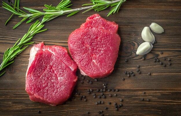 Deux steaks de bœuf cru à l'ail et au poivre sur une table en bois