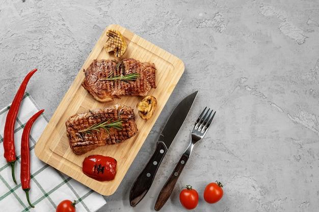 Deux steaks de boeuf grillés sur planche de bois, vue du dessus