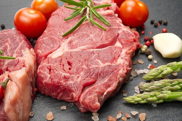 Deux steaks de boeuf marbrés crus avec des épices et des légumes