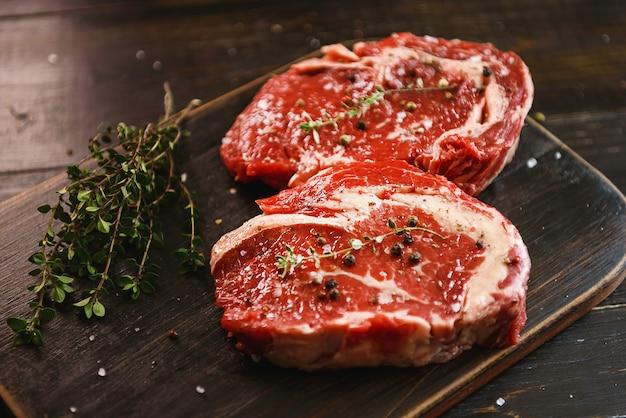 Deux steaks de bœuf marbrés à l'huile d'olive et aux épices prêts à être cuits.