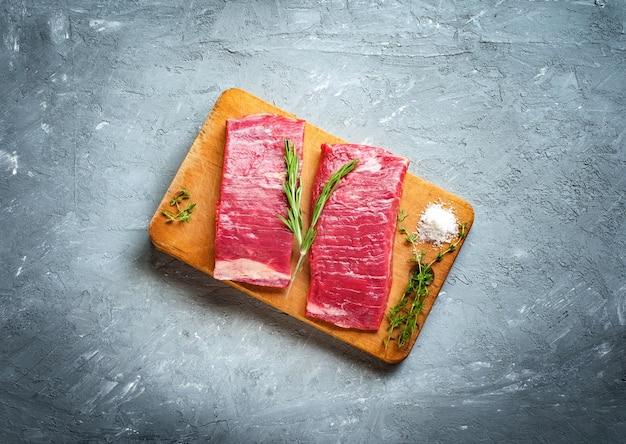 Deux steaks bruts sur planche de bois