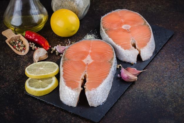 Deux steaks de saumon cru frais sur l'ardoise avec du sel, des poivrons, du citron sur une table sombre, vue de dessus. concept de régime alimentaire sain