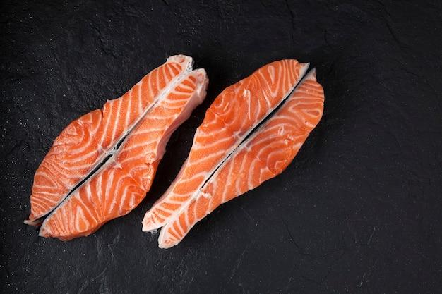 Deux steaks de saumon cru sur une texture noire