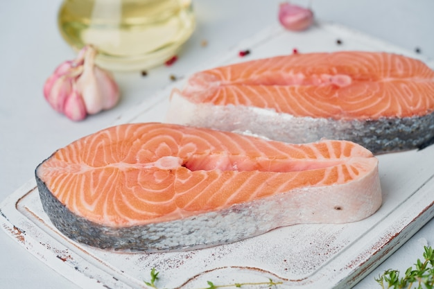 Deux steaks de saumon crus, filet de poisson, grandes tranches sur une planche à découper sur la table