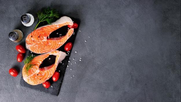 Deux steaks de saumon crus sur fond sombre