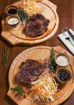 Deux steaks de viande avec des légumes et de verdure sur une table en bois dans un restaurant de luxe