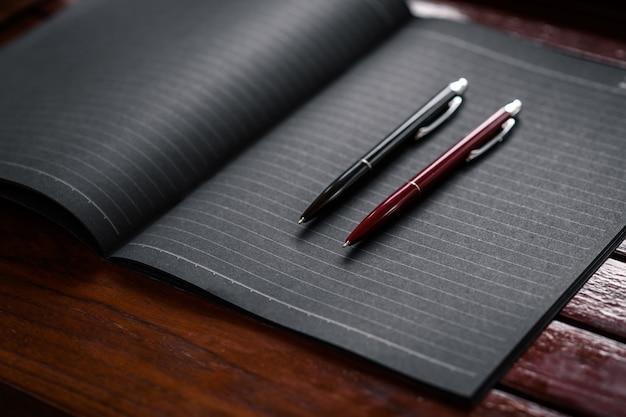 Deux stylos de bureau en noir et rouge situés sur un cahier noir posé sur une table en bois