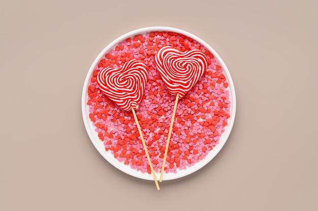 Deux sucettes en forme de coeur sur plaque blanche avec saupoudrage de confiserie rouge et rose. fond beige. concept vacances saint-valentin. mise à plat, vue de dessus
