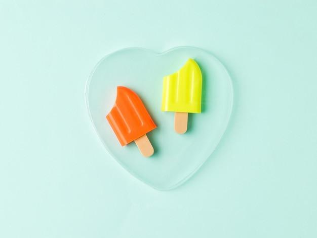 Deux sucettes glacées mordues dans un cœur en verre sur fond bleu. une collation estivale populaire.