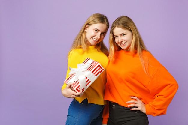 Deux superbes filles jumelles blondes vêtues de vêtements vifs tiennent une boîte cadeau à rayures rouges avec un ruban cadeau isolé sur un mur bleu violet. anniversaire de la famille des gens, concept de vacances.