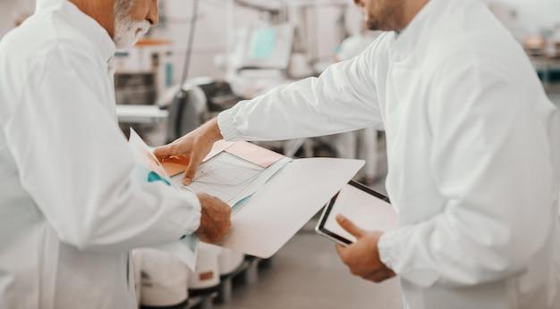 Deux superviseurs assidus vérifiant les statistiques tout en se tenant dans l'usine alimentaire. un plus jeune tenant une tablette. tous deux sont vêtus d'uniformes blancs stériles.