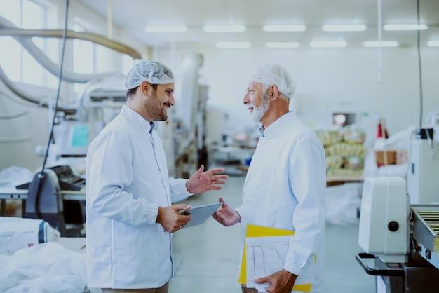 Deux superviseurs caucasiens souriants en uniformes stériles blancs debout dans une usine alimentaire et parlant de la qualité des aliments. un plus jeune tenant une tablette tandis qu'un ancien dossier contenant des documents sous l'aisselle