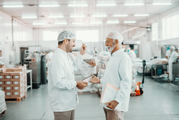 Deux superviseurs parlent de la qualité de la nourriture. un plus jeune tenant une tablette tandis qu'un ancien dossier contenant des graphiques. tous deux sont vêtus d'uniformes stériles et ont des filets à cheveux. intérieur de l'usine alimentaire.