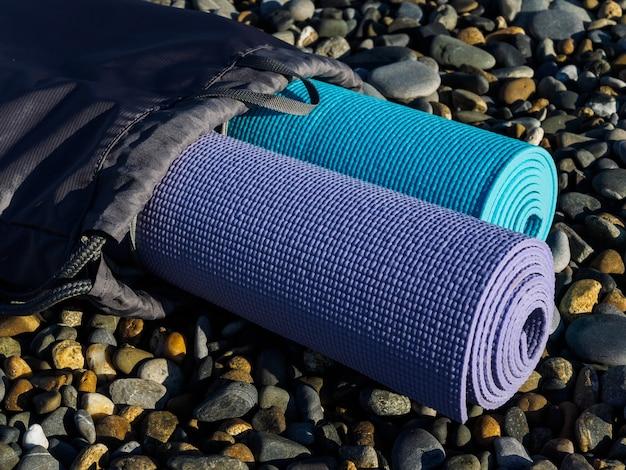 Deux tapis de yoga sur des galets de mer