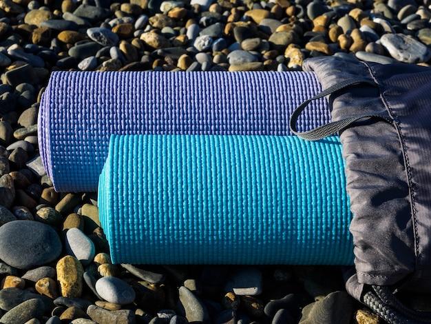 Deux tapis de yoga sur gros plan de galets de mer